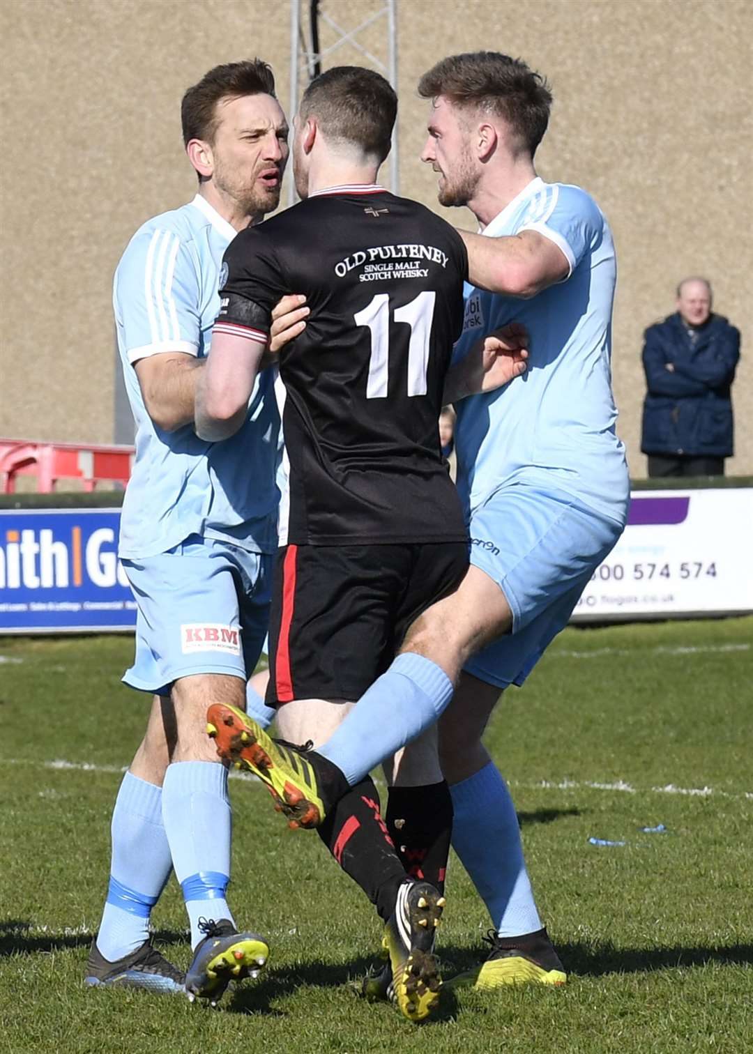 Wick Academy's Davie Allan is manhandled by Keith's Jamie McAllister while appearing to be kicked by Callum Porteous. Picture: Mel Roger