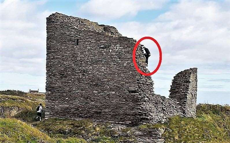 The image of a tourist climbing the Castle of Old Wick created anger in the community.Picture: Derek Bremner
