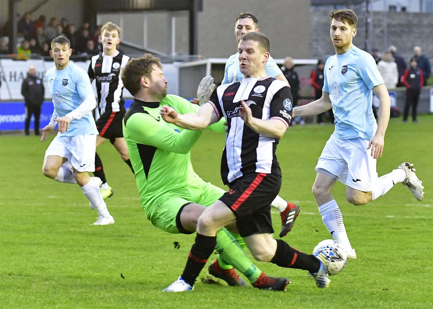 David Allan goes into a crunching challenge with Fraserburgh keeper Paul Leask during Wick Academy's 2-0 defeat at home to Broch. Picture: Mel Roger