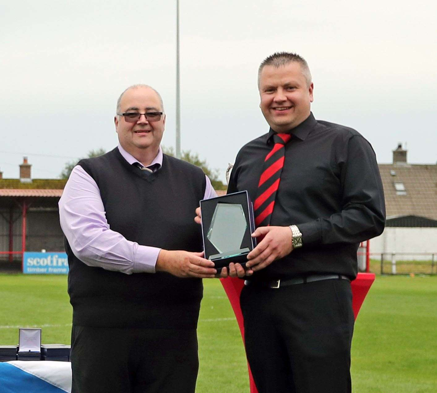 Wick Groats manager Kevin Anderson receives a memento of the match from Hugh Morrison, president of the Scottish AFA Highland executive committee. Picture: James Gunn
