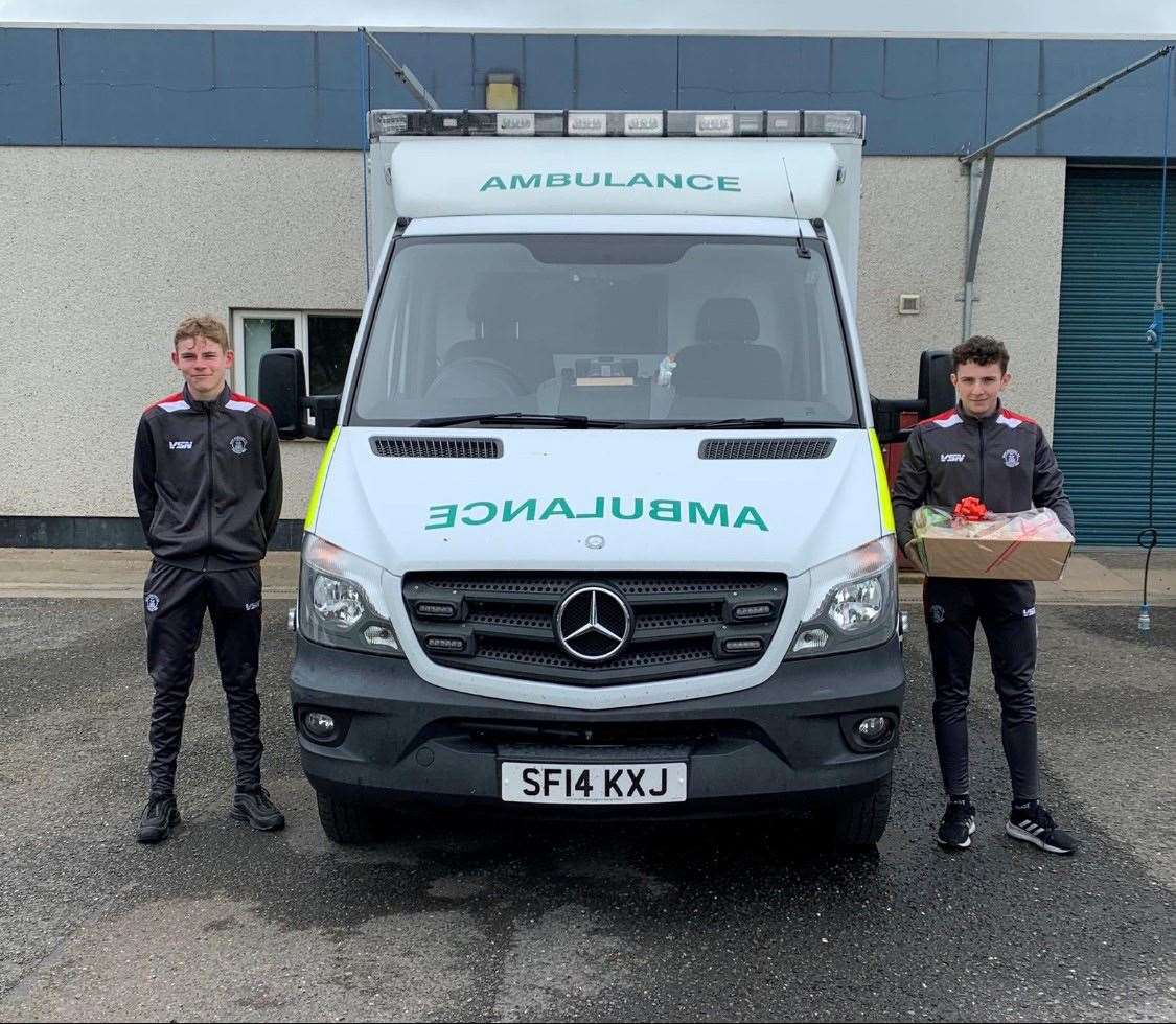 Alan Mathieson and Michael Steven of Wick Academy U17s handing over the hamper for the Wick ambulance crew.